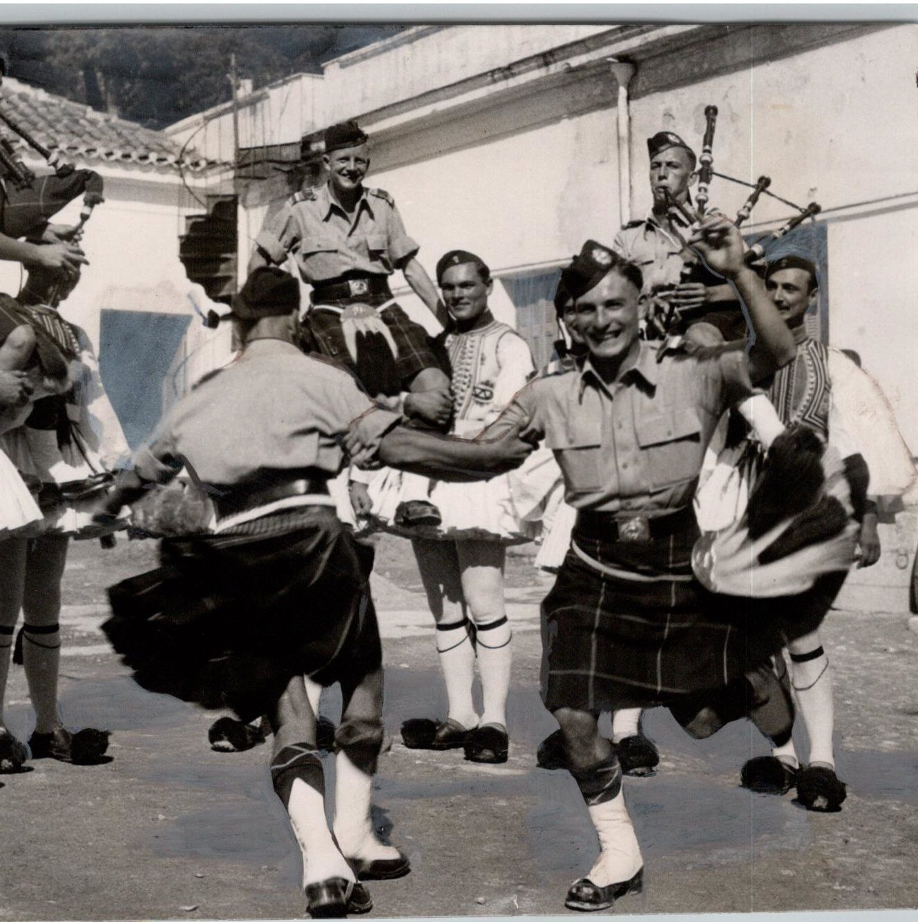 Scots and Greeks make merry in Athens during a visit of five men of the Highland Light Infantry to the barracks of the kilted Evzones, Palace Guard. 22/10/1946