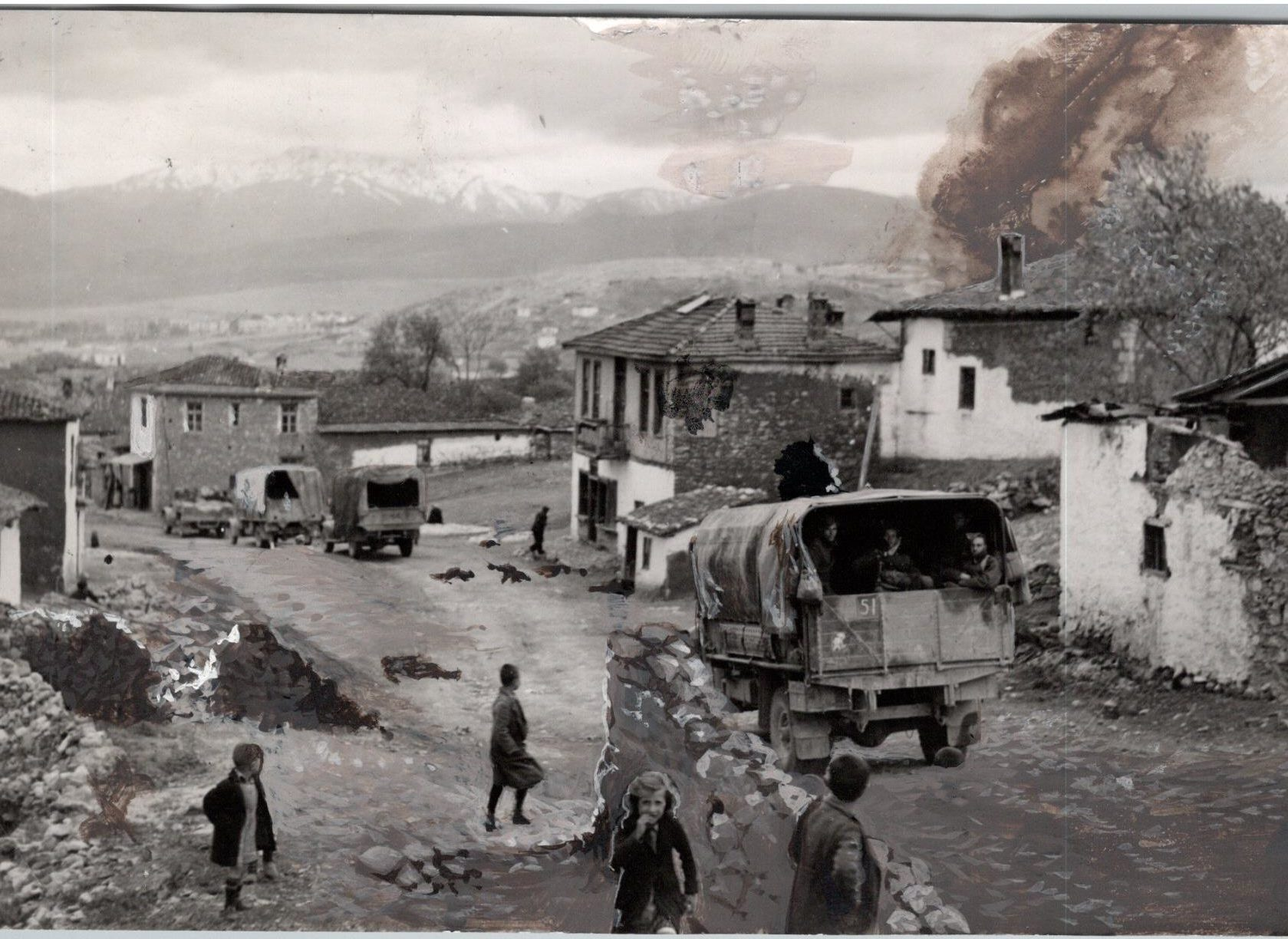 An Australian Convoy passing through a war-scarred Greek village.